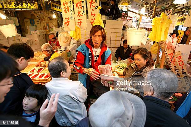 Fishmongers shout as they sell tuna at a fish stall in the Ameya Yokocho street market on December 31 2008 in Tokyo Japan People shop around in...