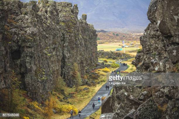 fissure zone with iceland flag at thingvellir national park, iceland - tectonic stock photos and pictures
