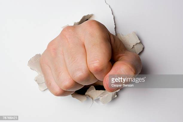 A fist breaking through a wall