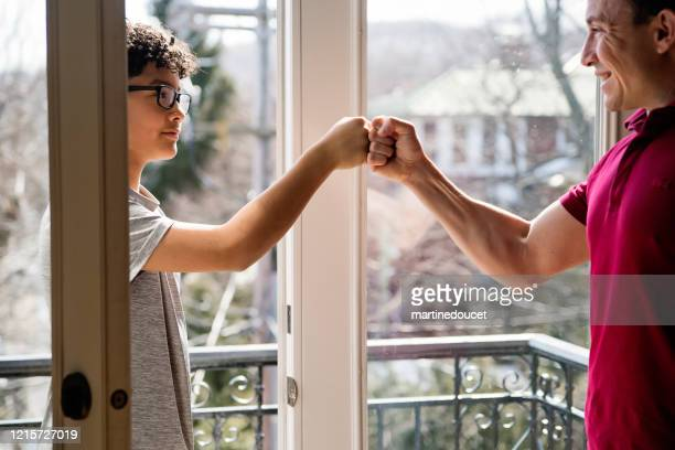 """fist bump between teenage boy and step-father, covid-19. - """"martine doucet"""" or martinedoucet stock pictures, royalty-free photos & images"""