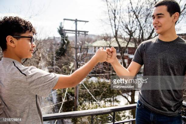 "fist bump between teenage brothers, covid-19. - ""martine doucet"" or martinedoucet stock pictures, royalty-free photos & images"