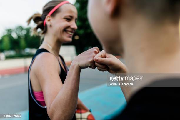 fist bump greeting - zusammenarbeit stock-fotos und bilder