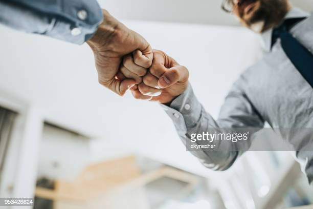 fist bump greeting! - fist bump stock pictures, royalty-free photos & images