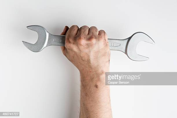 a fist holding a wrench up triumphantly - gripping stock pictures, royalty-free photos & images
