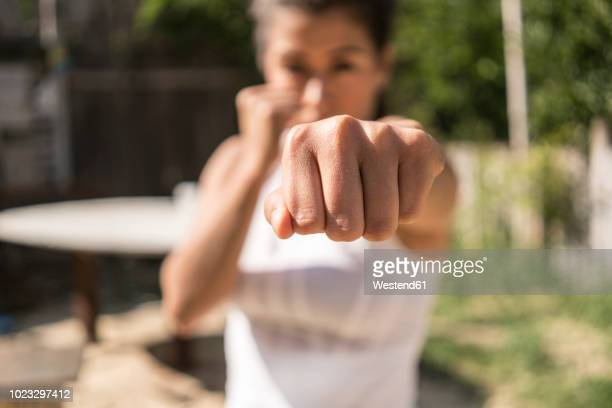 fist of selfdefending young woman, close-up - assertiveness stock pictures, royalty-free photos & images