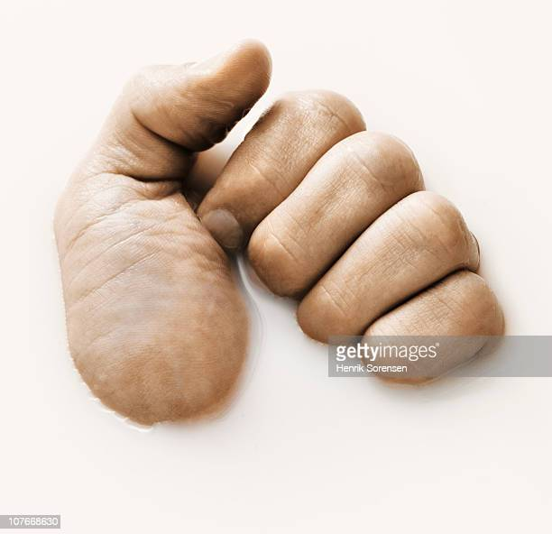Fist partly submerged in white liquid