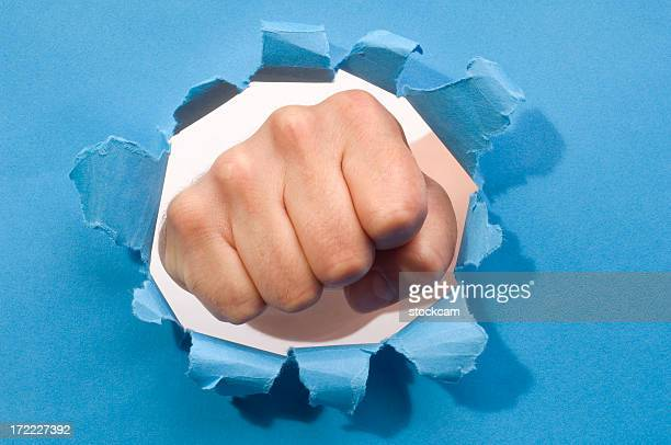 Fist punching through a ripped hole in a paper