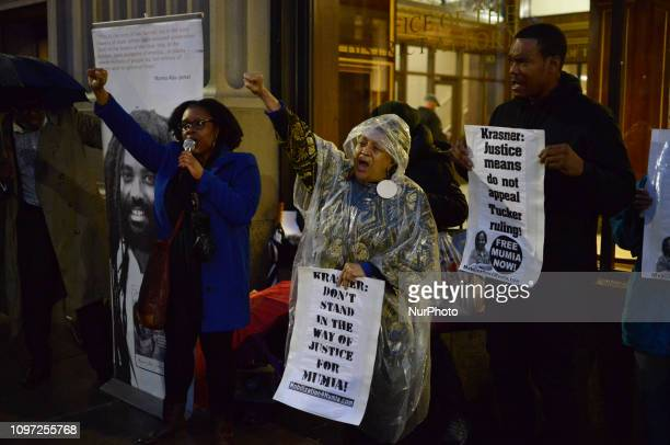 Fists are raised as activists Megan Malachi Pam Africa and Diop Olugbala with two dozen others rally outside the District Attorneys Office in...
