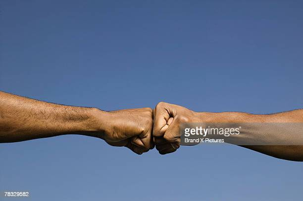 fists bumping - fist bump stock pictures, royalty-free photos & images