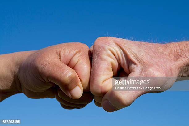 Fists pound against each other on a blue background