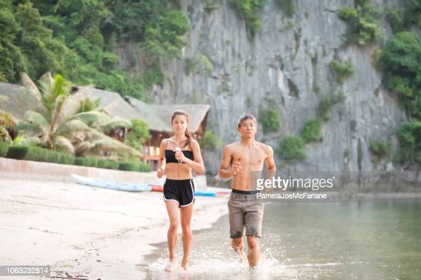 fit asian father and daughter running together on tropical beach, vietnam - pretty vietnamese women stock pictures, royalty-free photos & images