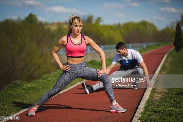 fit athlete couple doing stretching exercises outdoors. - emir memedovski stock pictures, royalty-free photos & images