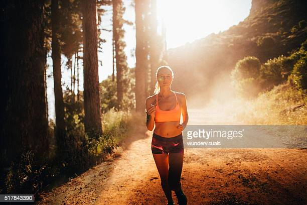 Fit athletic woman running on a sunlit mountain dirt path