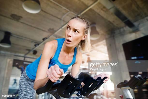 Fit aantrekkelijke vrouw in blauwe tanglet fietsen op hometrainer