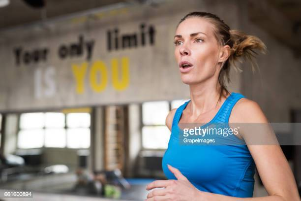 Fit attractive woman in blue tanglet running on treadmill in modern gym