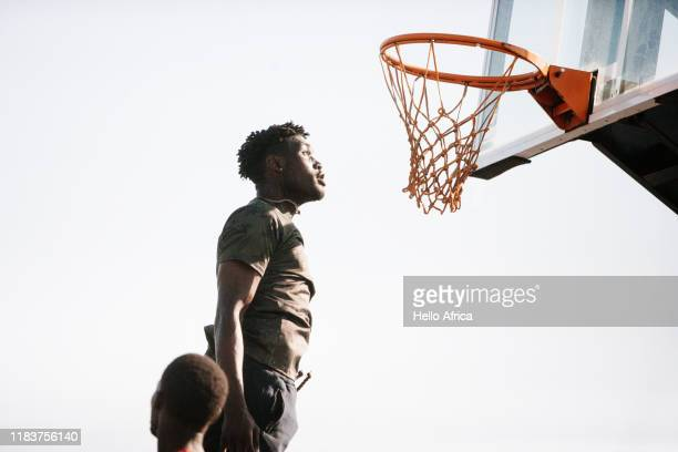 Fit basketball player jumping very high to look at the hoop
