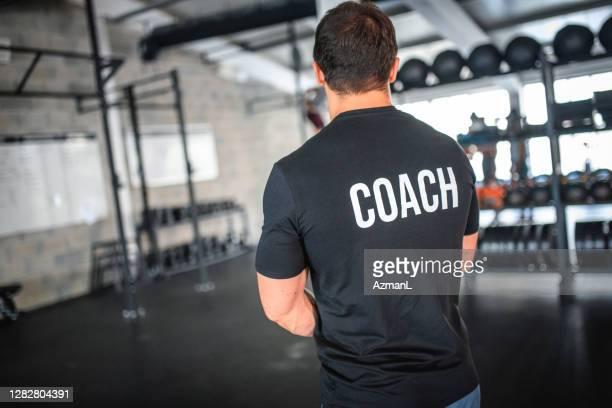 adatta allenatore maschile caucasico in piedi nella palestra di allenamento incrociato - top nero foto e immagini stock