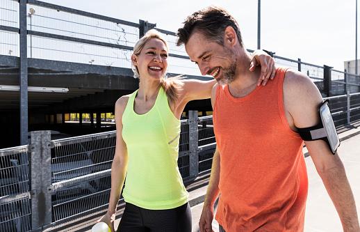 Fit couple jogging in the city, having fun, taking a break - gettyimageskorea