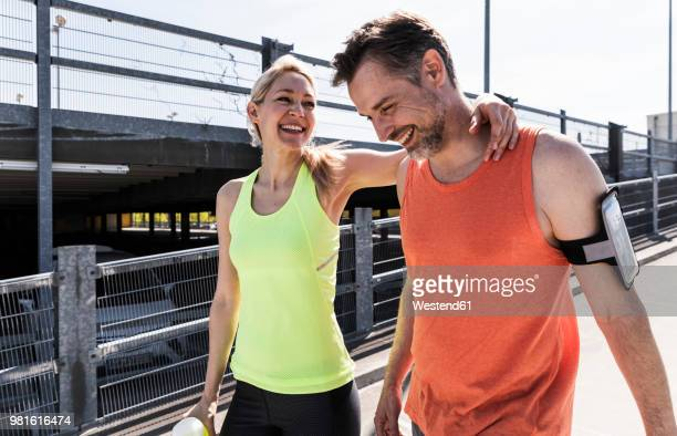 fit couple jogging in the city, having fun, taking a break - sportkleidung stock-fotos und bilder