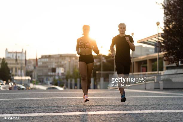 Fit couple jogging, sunset in background.