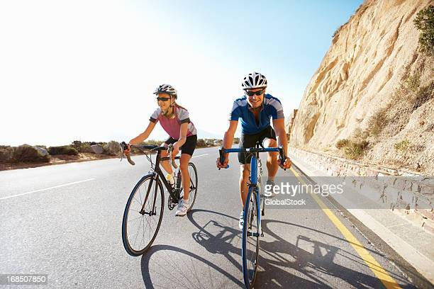 fit couple riding bicycles in the countryside - racing bicycle stock pictures, royalty-free photos & images