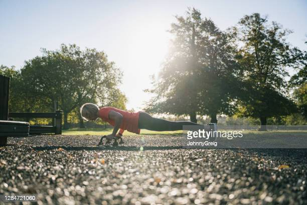 fit early 50s female athlete doing push-ups with grips - clapham common stock pictures, royalty-free photos & images