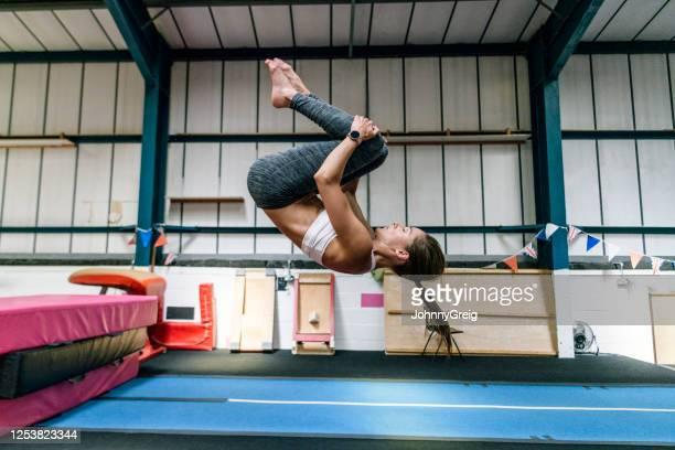 athlète féminine en forme au début des années 30 pratiquant flip dans la salle de gym - gymnastique au sol photos et images de collection