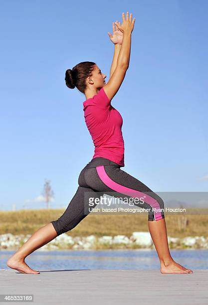 fit female does yoga near a lake - yoga pants stock photos and pictures