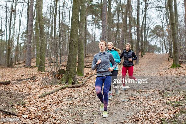 Fit female friends jogging in forest
