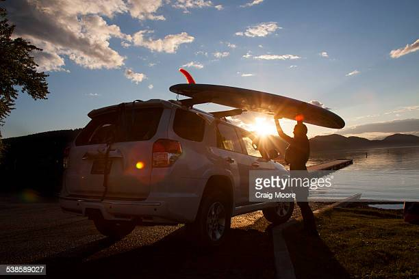 A fit female places her stand up paddle board on a car at sunset on Whitefish Lake in Montana.