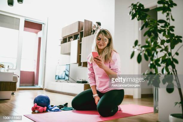 fit female stretching at home on exercise mat and taking selfie on smartphone - home workout stock pictures, royalty-free photos & images