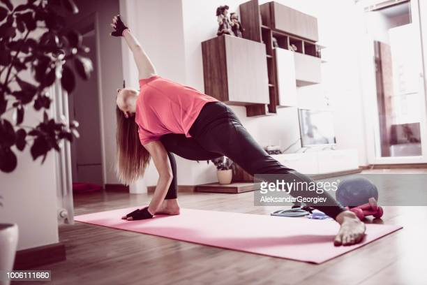 fit female stretching on exercise mat at home - sports glove stock pictures, royalty-free photos & images