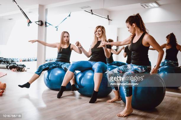 Fit Females Doing A Balance Exercise With Fitness Ball In Gym