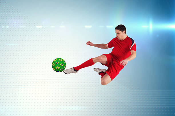 Composite image of fit football player jumping and kicking