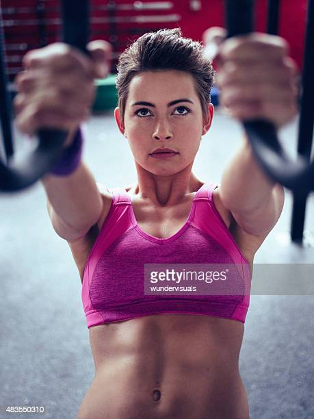 fit girl exercising her abdominal muscles with gymnastic rings - daily sport girls stock pictures, royalty-free photos & images