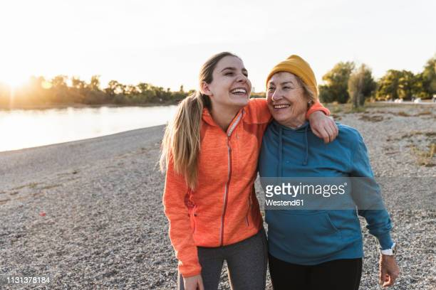 fit grandmother and granddaughter walking at the river with arms around, having fun - estilo de vida ativo imagens e fotografias de stock