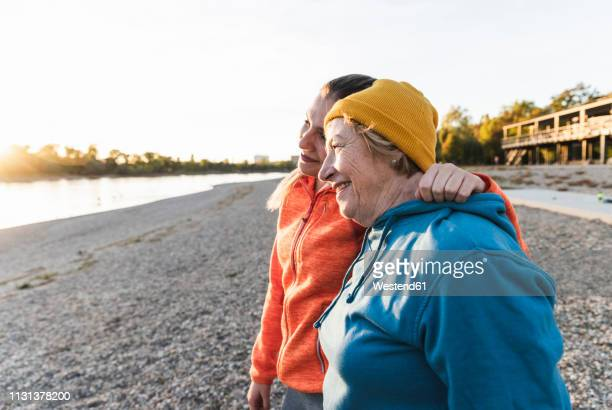 fit grandmother and granddaughter walking at the river with arms around, having fun - contemplation family stock pictures, royalty-free photos & images