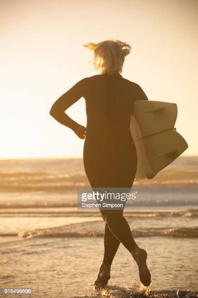 fit gray-haired woman surfer in wetsuit running into the ocean