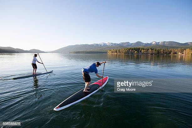 A fit male and female stand up paddle board (SUP) at sunset on Whitefish Lake in Whitefish, Montana.