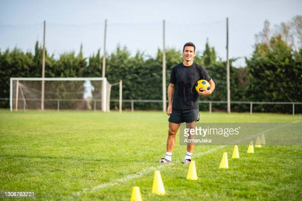 fit male footballer in early 40s ready to coach drills - coach stock pictures, royalty-free photos & images