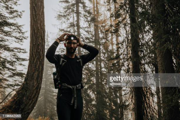 fit male hiker with a headlamp - endurance race stock pictures, royalty-free photos & images