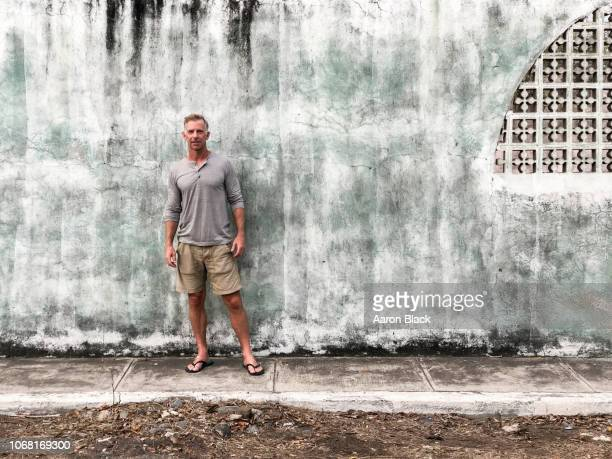 Fit male in his 50's standing in front of a textured cement wall in a third world country.