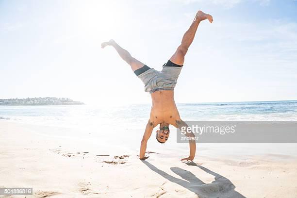 Fit man doing a cartwheel at the beach