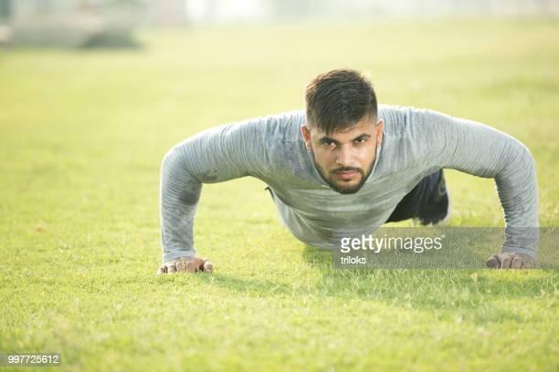 young indian man doing pushups grass