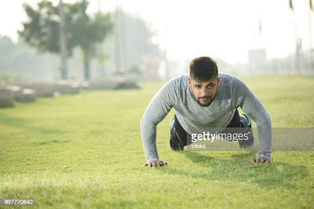 young indian man doing pushups grass