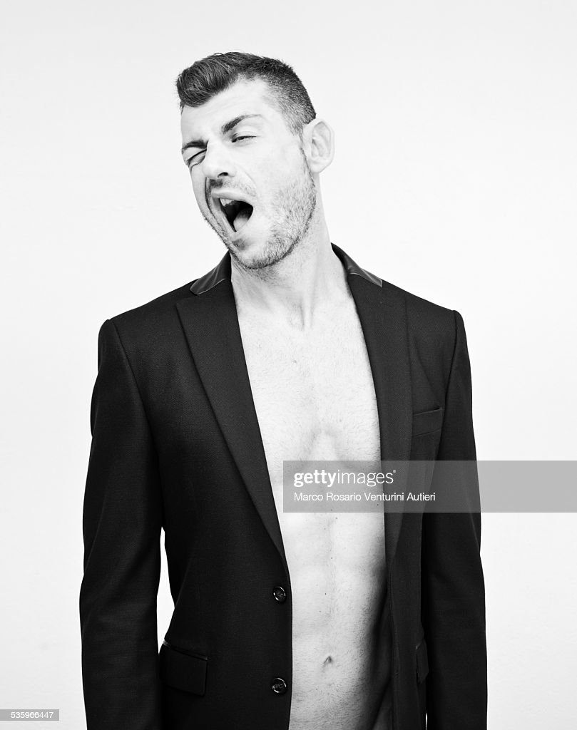 Fit man, dressed with night jacket only, pulling funny faces : Stock Photo