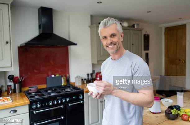 fit man eating a healthy breakfast before his workout - mature men stock pictures, royalty-free photos & images