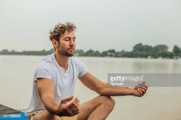 fit man exercising yoga - zen like stock pictures, royalty-free photos & images
