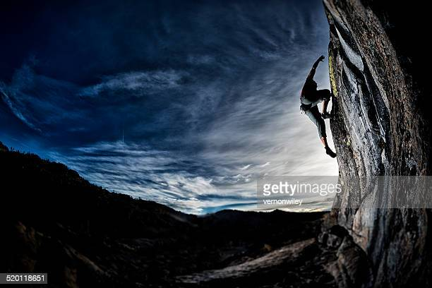 Fit man rock climbing al atardecer