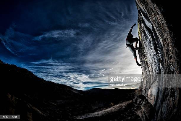Fit man rock climbing at sunset
